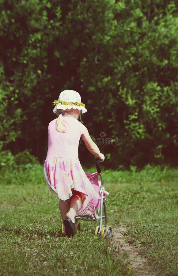 Χαριτωμένο παιχνίδι μικρών κοριτσιών με τη μεταφορά μωρών της στο λιβάδι την ηλιόλουστη θερινή ημέρα στοκ εικόνες