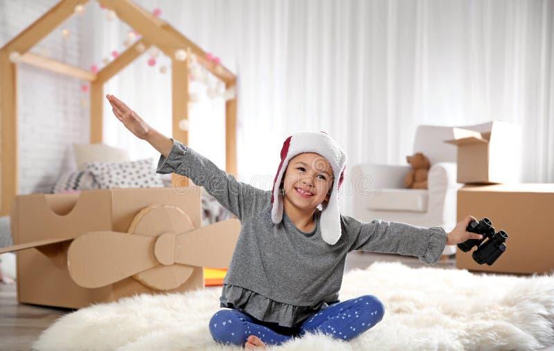 Χαριτωμένο παιχνίδι μικρών κοριτσιών με τις διόπτρες και το αεροπλάνο χαρτονιού στοκ εικόνα με δικαίωμα ελεύθερης χρήσης