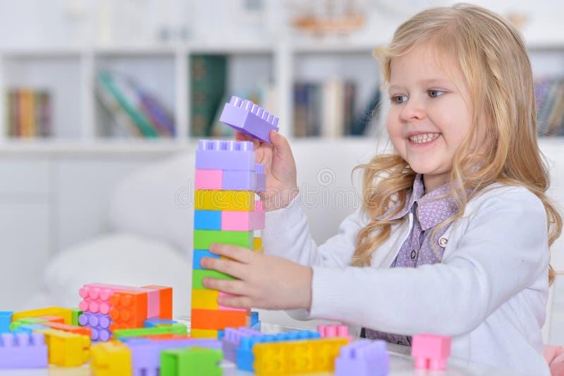 Χαριτωμένο παιχνίδι μικρών κοριτσιών με τους ζωηρόχρωμους πλαστικούς φραγμούς στοκ φωτογραφία