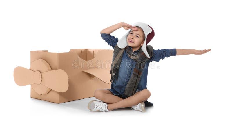 Χαριτωμένο παιχνίδι μικρών κοριτσιών με το αεροπλάνο χαρτονιού στο λευκό στοκ εικόνες