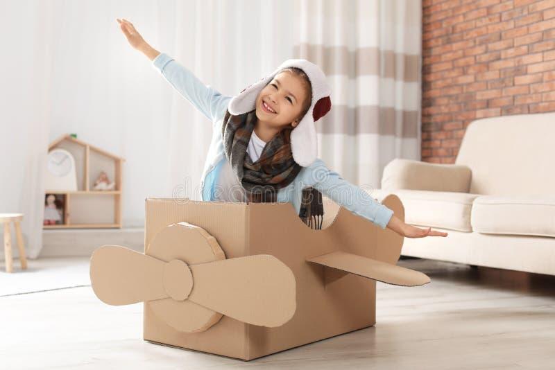 Χαριτωμένο παιχνίδι μικρών κοριτσιών με το αεροπλάνο χαρτονιού στοκ εικόνα με δικαίωμα ελεύθερης χρήσης