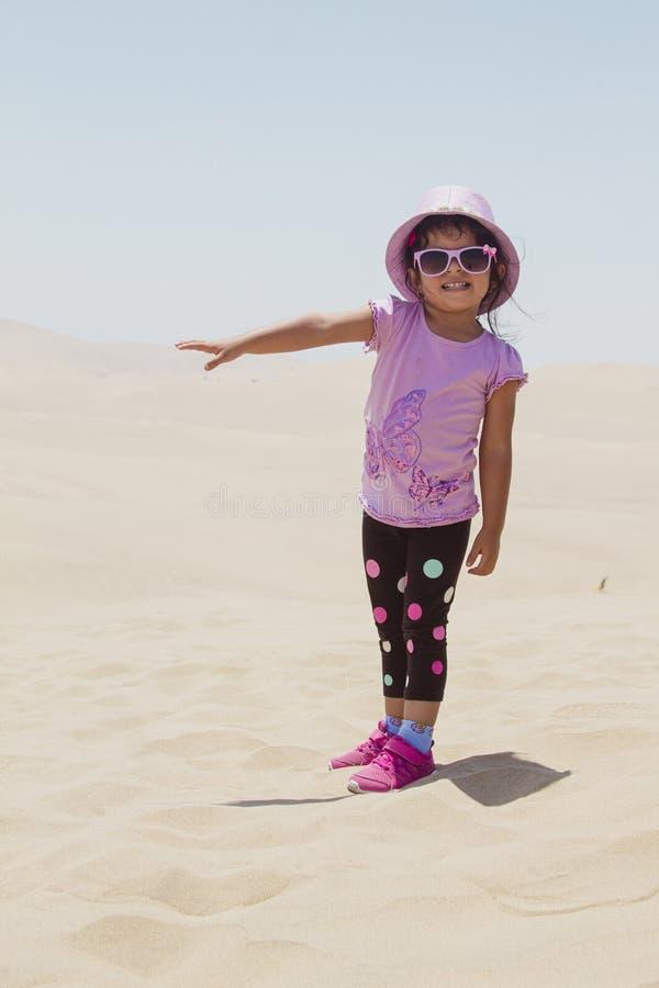 Χαριτωμένο παιχνίδι μικρών κοριτσιών στους αμμόλοφους στοκ φωτογραφία με δικαίωμα ελεύθερης χρήσης