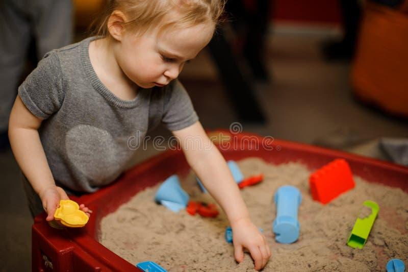 Χαριτωμένο παιχνίδι μικρών κοριτσιών στο Sandbox στοκ φωτογραφία