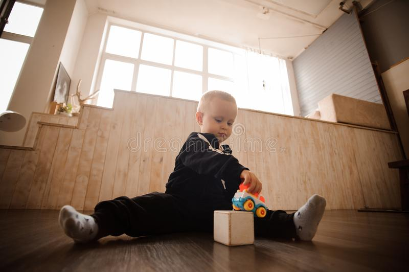 Χαριτωμένο παιχνίδι μικρών παιδιών με τα παιχνίδια στο πάτωμα στοκ φωτογραφίες