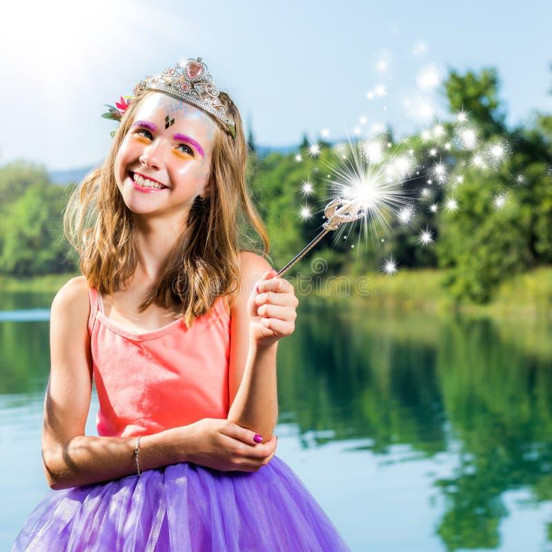 Χαριτωμένο παιχνίδι κοριτσιών με τη μαγική ράβδο στη λίμνη στοκ εικόνες