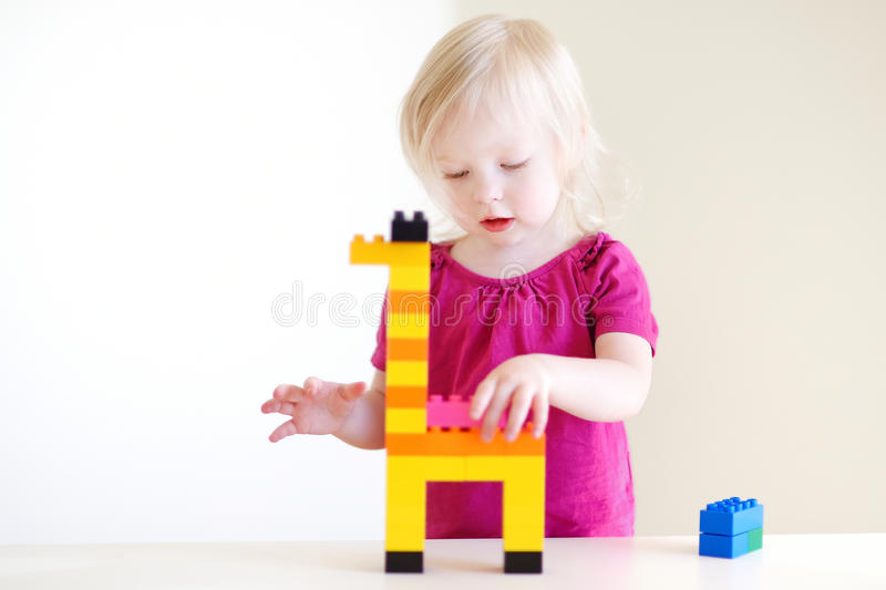 Χαριτωμένο παιχνίδι κοριτσιών μικρών παιδιών με τους ζωηρόχρωμους φραγμούς στοκ φωτογραφία