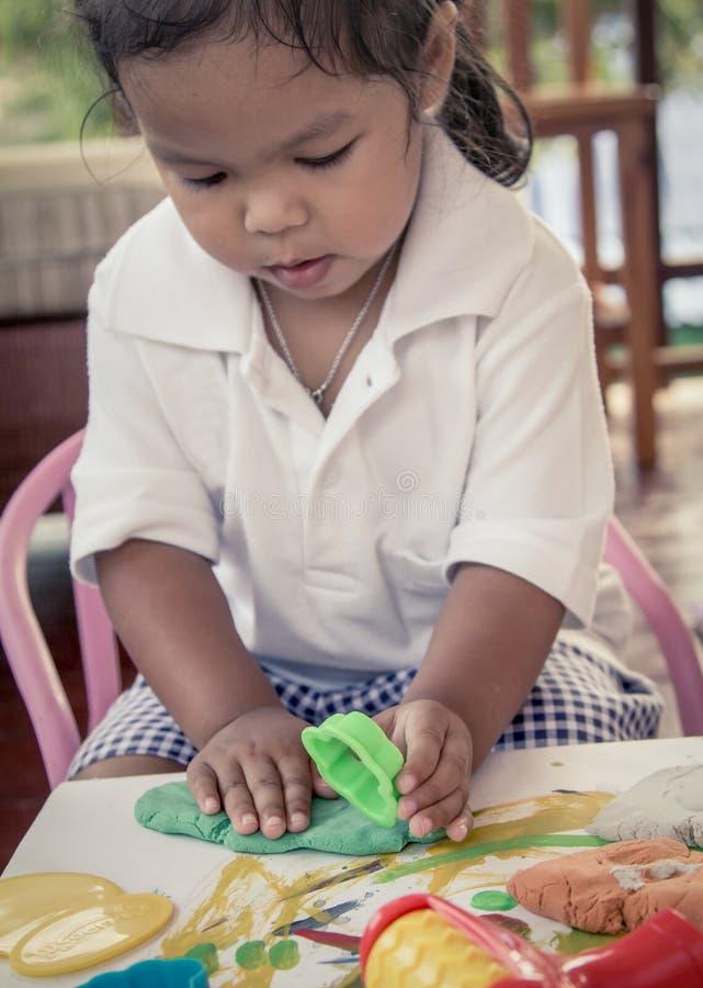 Χαριτωμένο παιχνίδι μικρών κοριτσιών παιδιών με τον άργιλο, παιχνίδι doh στοκ εικόνα με δικαίωμα ελεύθερης χρήσης