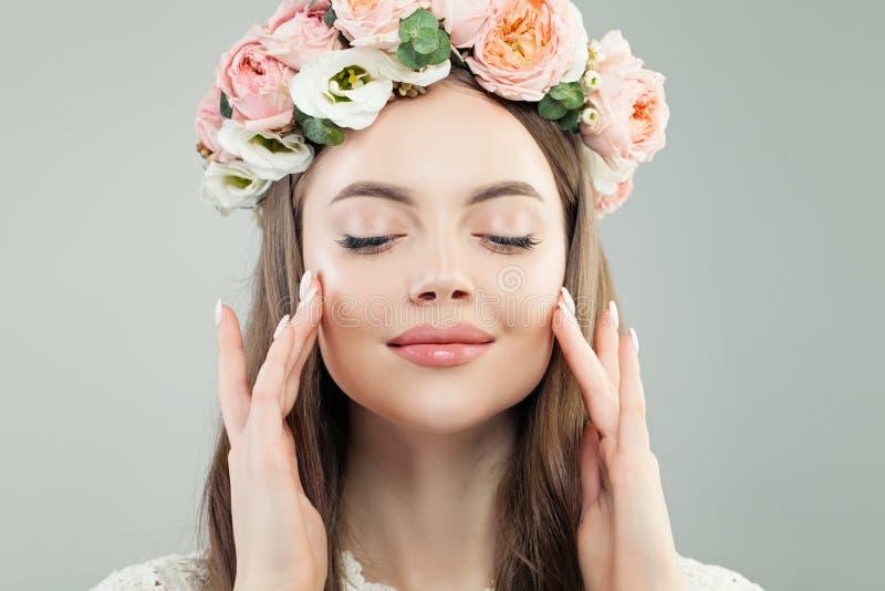 Χαριτωμένο πρότυπο πρόσωπο γυναικών Φυσικά Makeup και λουλούδια, Skincare και του προσώπου έννοια επεξεργασίας στοκ εικόνα
