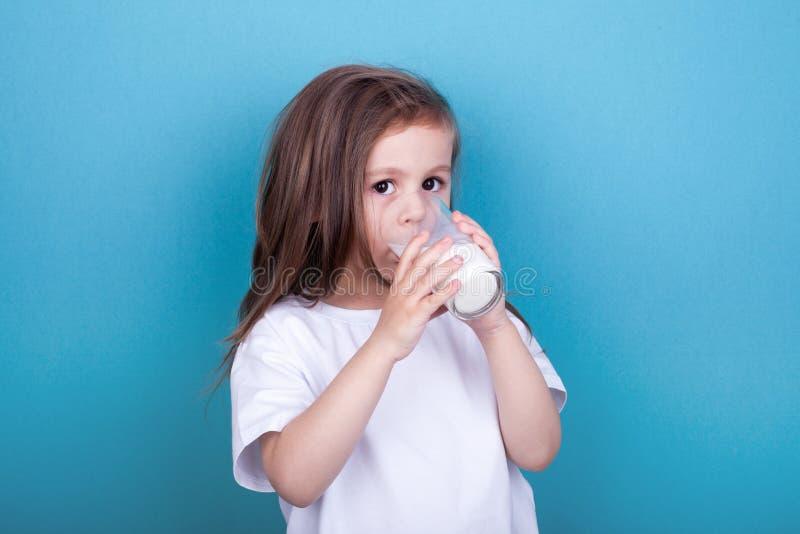 Χαριτωμένο πόσιμο γάλα μικρών κοριτσιών από το γυαλί στοκ εικόνα