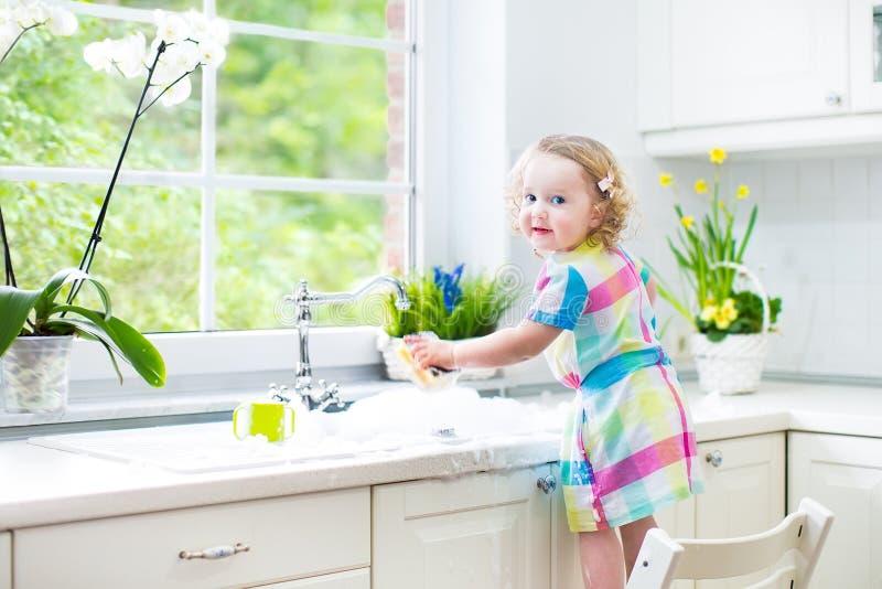 Χαριτωμένο σγουρό κορίτσι μικρών παιδιών στα ζωηρόχρωμα πιάτα πλύσης φορεμάτων στοκ φωτογραφίες