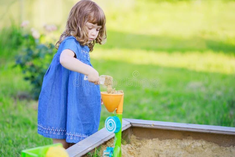 Χαριτωμένο σγουρό παιχνίδι μικρών κοριτσιών στο Sandbox στοκ φωτογραφίες