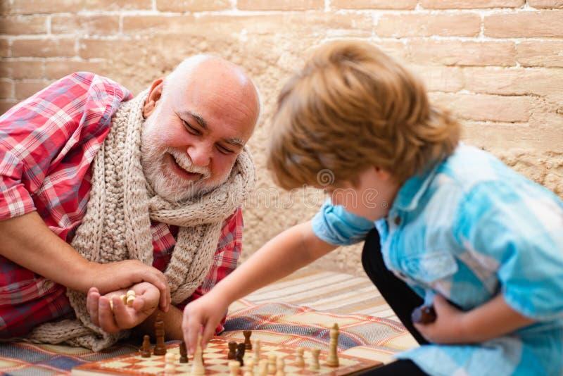 Χαριτωμένο σκάκι παιχνιδιού μικρών παιδιών o Χαριτωμένο σκάκι παιχνιδιού μικρών παιδιών Γενεές Το όμορφοι grandpa και ο εγγονός ε στοκ εικόνες
