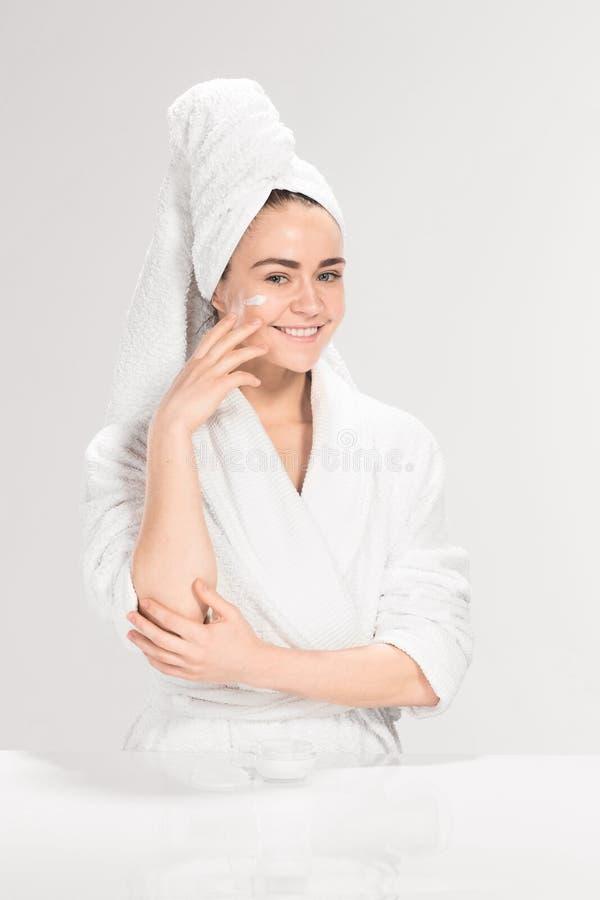 Χαριτωμένο συμπαθητικό κορίτσι με την κρέμα στο πρόσωπό της στοκ φωτογραφία με δικαίωμα ελεύθερης χρήσης