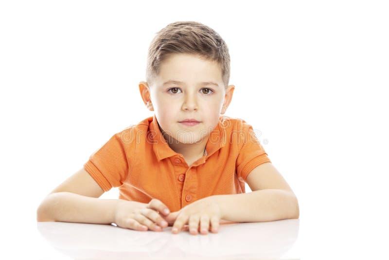 Χαριτωμένο σχολικό αγόρι σε μια πορτοκαλιά συνεδρίαση μπλουζών στον πίνακα E στοκ εικόνα
