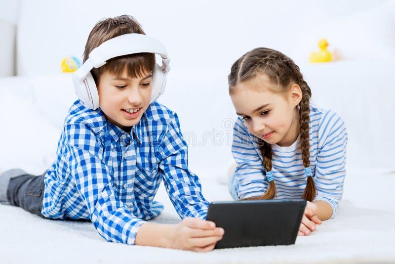 Χαριτωμένο τυχερό παιχνίδι παιδιών στην ταμπλέτα στοκ εικόνες