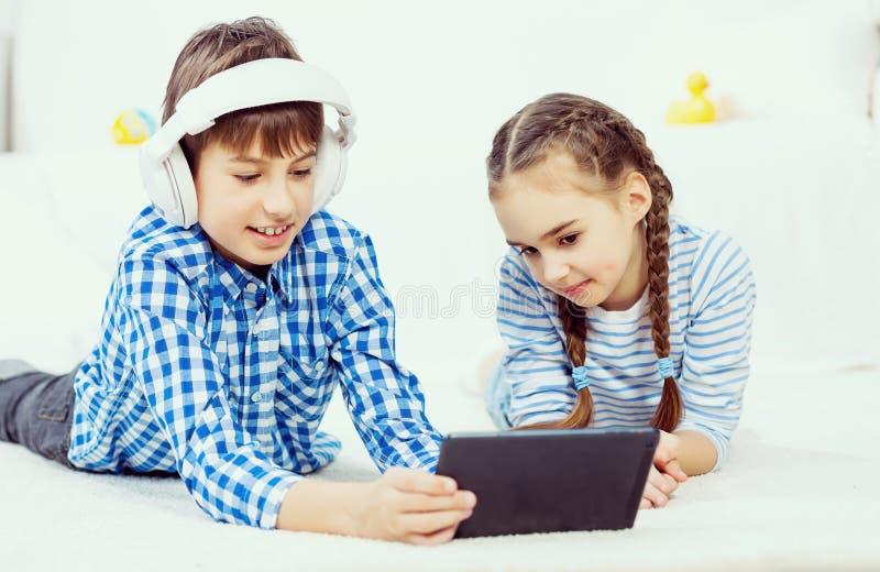 Χαριτωμένο τυχερό παιχνίδι παιδιών στην ταμπλέτα στοκ φωτογραφίες