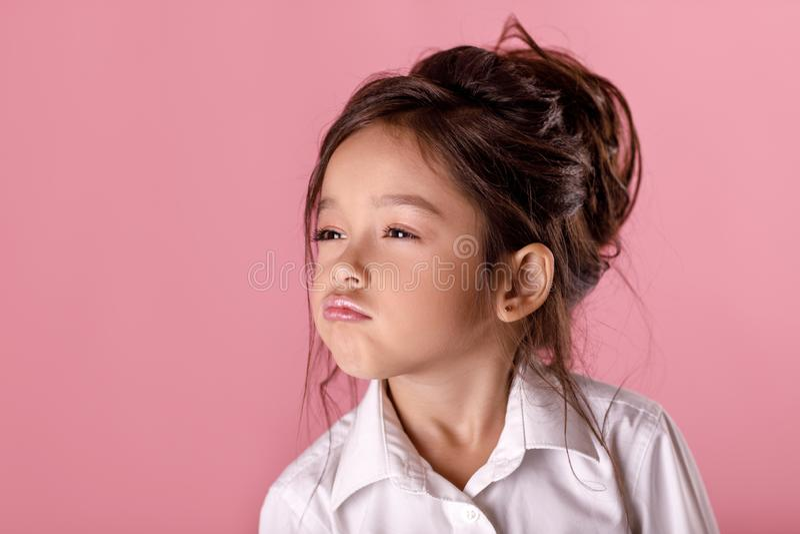Χαριτωμένο υπερήφανο μικρό κορίτσι στο άσπρο πουκάμισο στο ρόδινο υπόβαθρο Ανθρώπινες συγκινήσεις και έκφραση του προσώπου στοκ εικόνα
