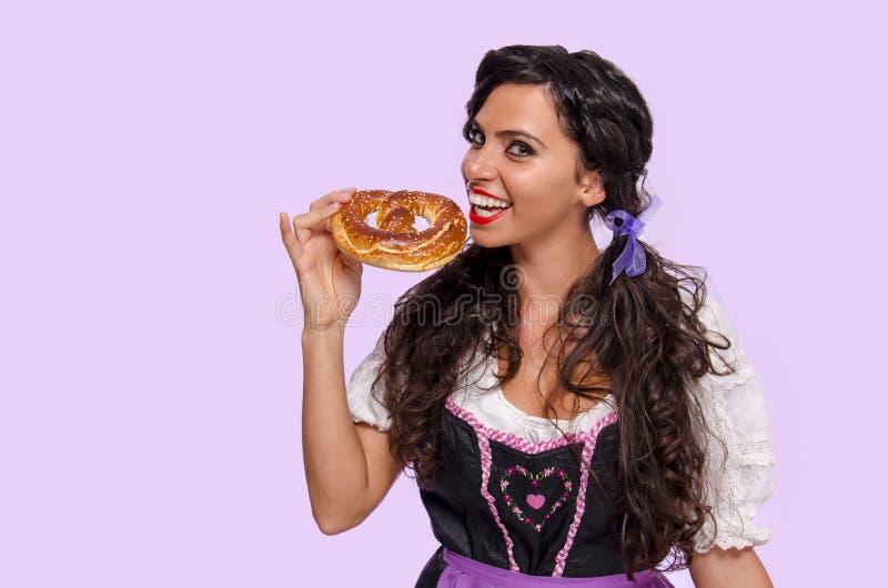Χαριτωμένο χαμογελώντας κορίτσι που τρώει βαυαρικό pretzel στοκ εικόνες