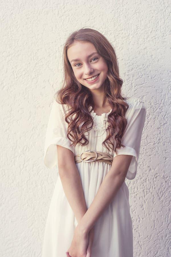 Χαριτωμένο χαμογελώντας κορίτσι στο άσπρο φόρεμα στοκ εικόνες