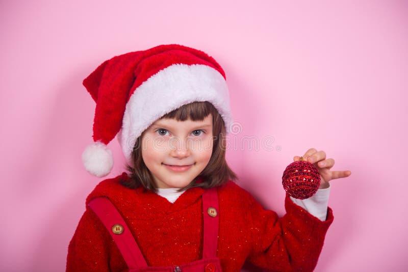 Χαριτωμένο χαμογελώντας μικρό κορίτσι στο καπέλο Santa και κοστούμι που κρατά την κόκκινη σφαίρα Χριστουγέννων στο στούντιο στο ρ στοκ εικόνα