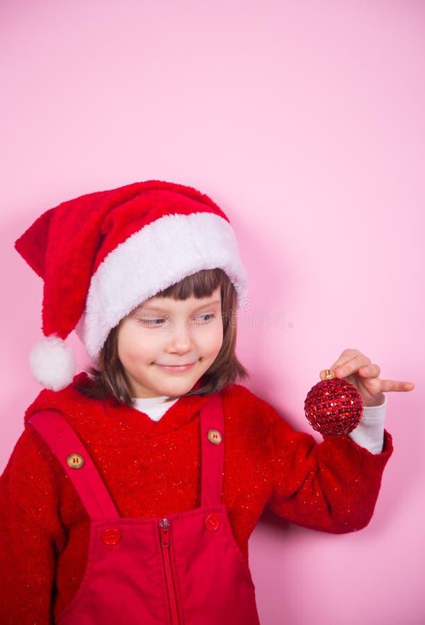 Χαριτωμένο χαμογελώντας μικρό κορίτσι στο καπέλο Santa και κοστούμι που κρατά την κόκκινη σφαίρα Χριστουγέννων στο στούντιο στο ρ στοκ εικόνα με δικαίωμα ελεύθερης χρήσης