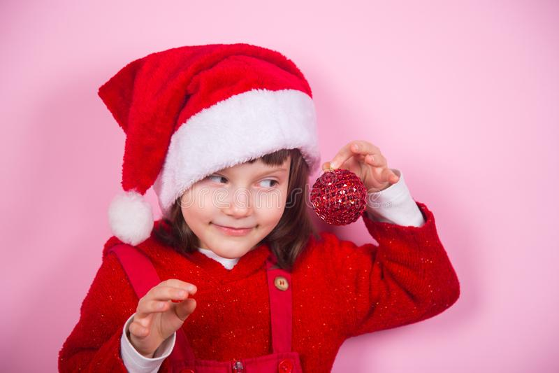 Χαριτωμένο χαμογελώντας μικρό κορίτσι στο καπέλο Santa και κοστούμι που κρατά την κόκκινη σφαίρα Χριστουγέννων στο στούντιο στο ρ στοκ φωτογραφία
