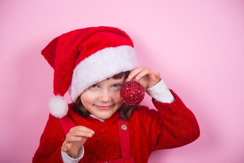 Χαριτωμένο χαμογελώντας μικρό κορίτσι στο καπέλο Santa και κοστούμι που κρατά την κόκκινη σφαίρα Χριστουγέννων στο στούντιο στο ρ στοκ φωτογραφίες