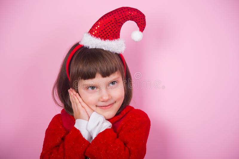 Χαριτωμένο χαμογελώντας μικρό κορίτσι στο καπέλο Santa και κοστούμι Χριστουγέννων στο στούντιο στο ρόδινο υπόβαθρο στοκ φωτογραφία με δικαίωμα ελεύθερης χρήσης
