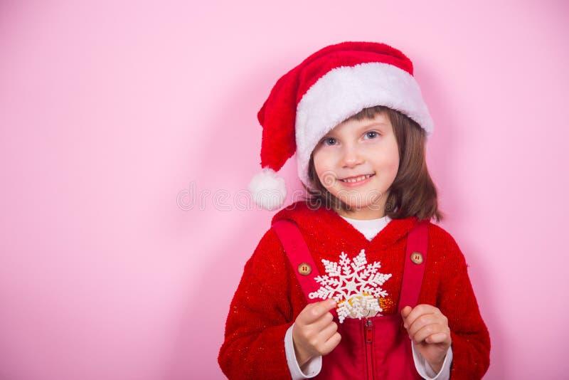 Χαριτωμένο χαμογελώντας μικρό κορίτσι στο καπέλο Santa και snowflake εκμετάλλευσης κοστουμιών Χριστουγέννων στο στούντιο στο ρόδι στοκ εικόνα