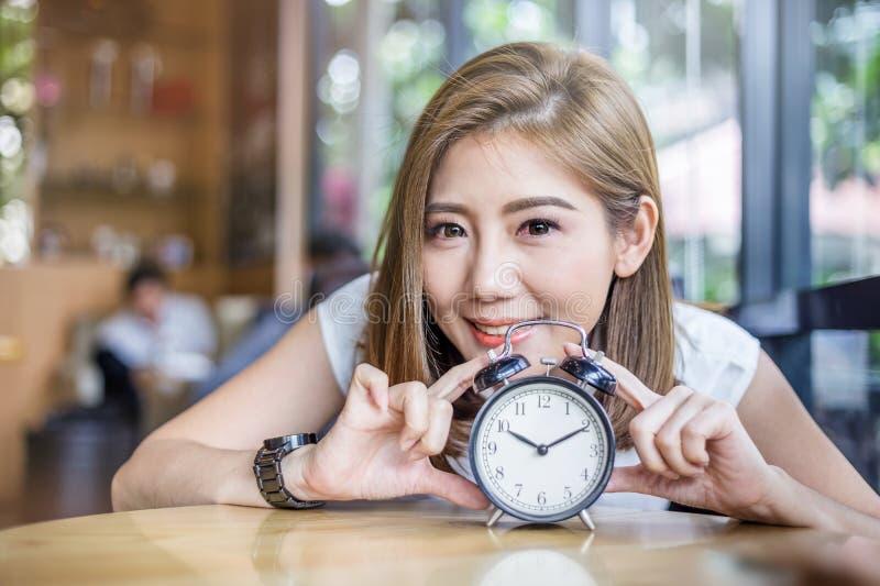 Χαριτωμένο χαμογελώντας κορίτσι με το ξυπνητήρι στον ξύλινο πίνακα στοκ εικόνες με δικαίωμα ελεύθερης χρήσης