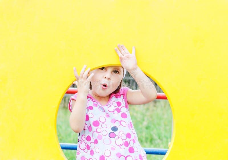 Χαριτωμένο χαμογελώντας κορίτσι που κρυφοκοιτάζει από το παράθυρο στοκ εικόνα με δικαίωμα ελεύθερης χρήσης