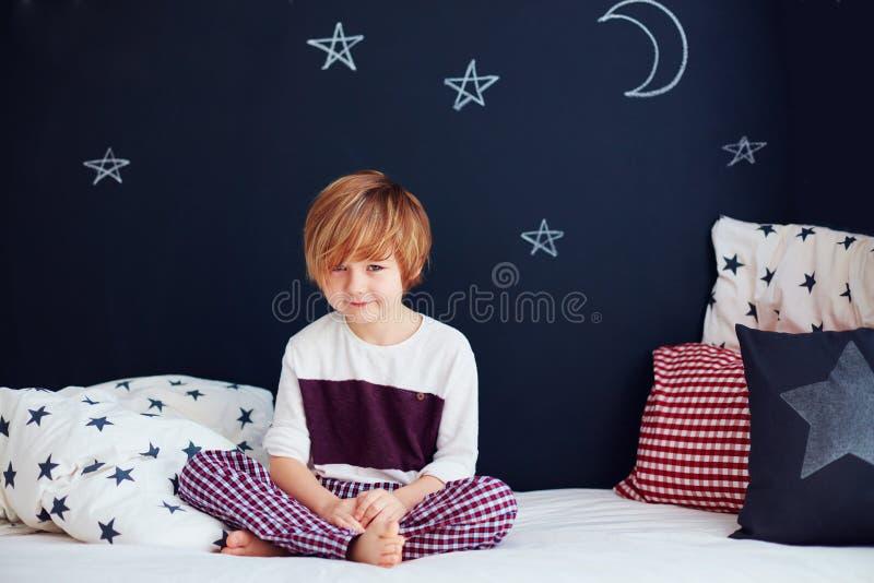 Χαριτωμένο χαμογελώντας παιδί στις πυτζάμες που κάθεται στο κρεβάτι στο δωμάτιο βρεφικών σταθμών στοκ εικόνα