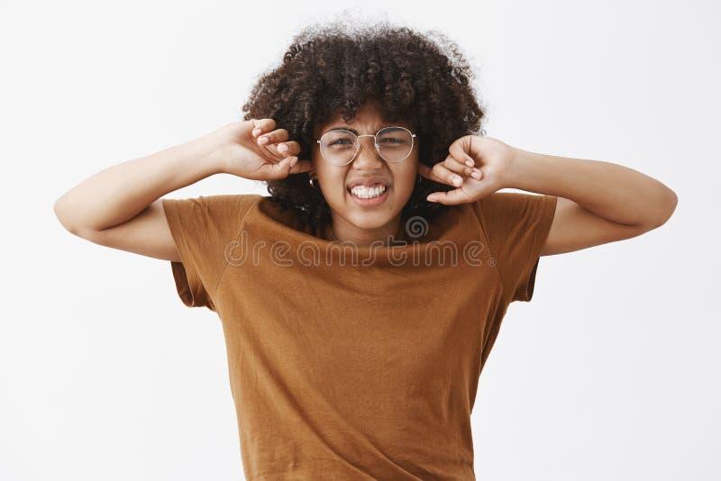 Χαριτωμένο όμορφο θηλυκό nerd με το afro hairstyle στα διαφανή ορισμένα γυαλιά που και που ζαρώνουν η μύτη στοκ εικόνα με δικαίωμα ελεύθερης χρήσης