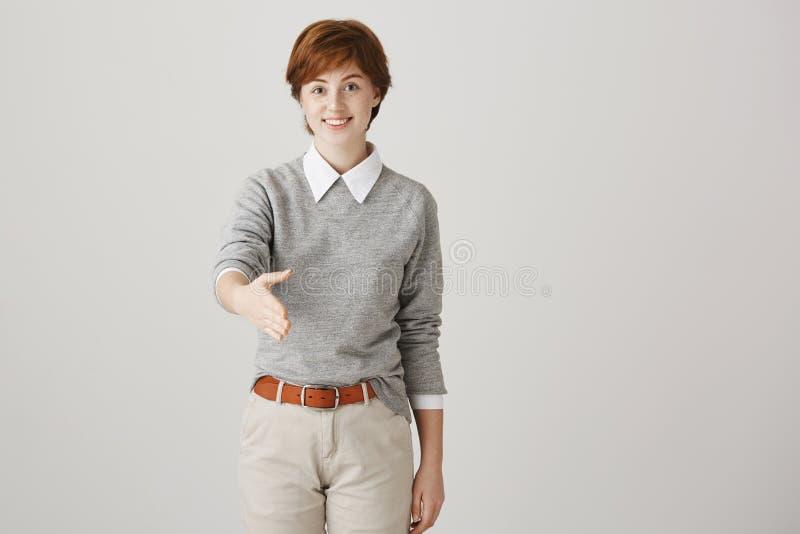 Χαριτωμένο όμορφο καυκάσιο redhead κορίτσι με το σύντομο κούρεμα και λατρευτό χέρι τεντώματος χαμόγελου προς τη κάμερα που δίνει στοκ εικόνα
