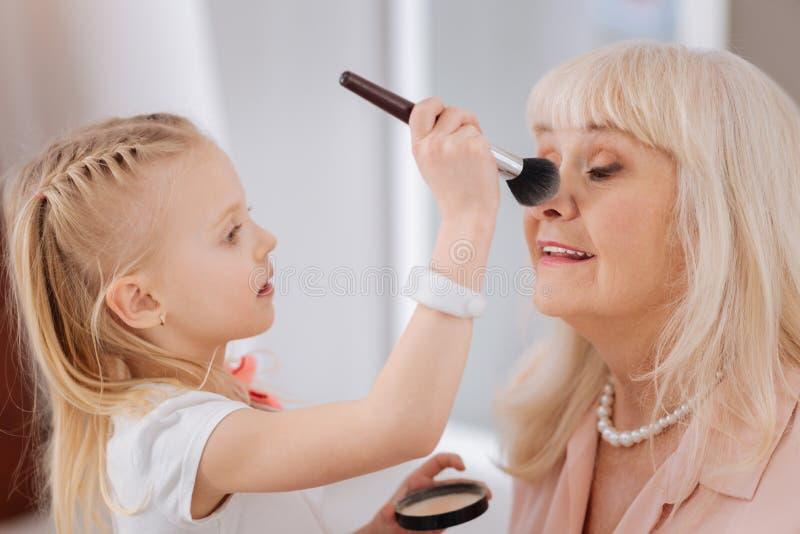 Χαριτωμένο όμορφο κορίτσι που βάζει τη σκόνη στη μύτη γιαγιάδων της στοκ φωτογραφίες με δικαίωμα ελεύθερης χρήσης