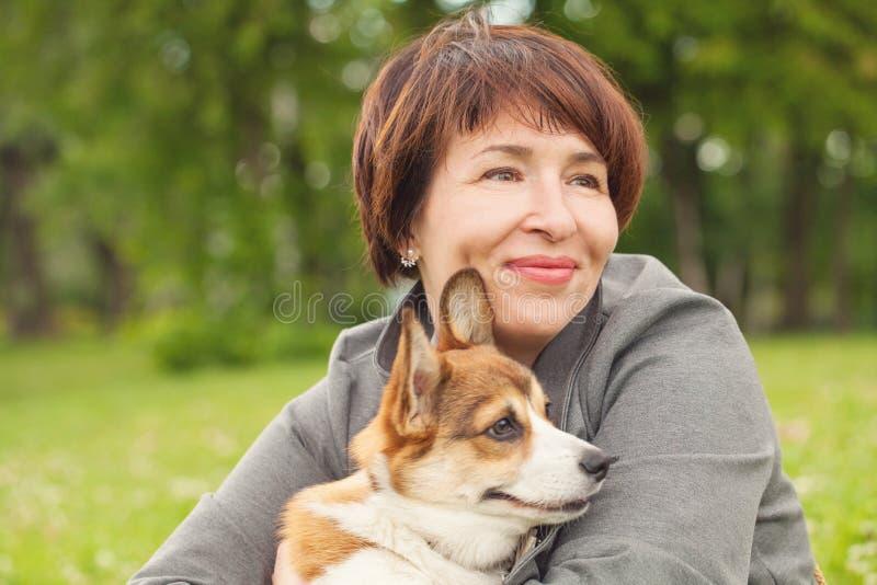 Χαριτωμένο ώριμο κατοικίδιο ζώο σκυλιών κουταβιών αγκαλιάς γυναικών στο θερινό πάρκο στοκ εικόνα