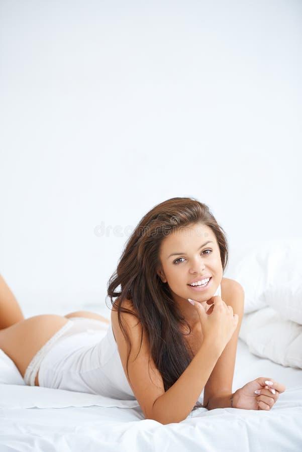 Χαριτωμένο brunette που βρίσκεται στο άσπρο κρεβάτι στοκ εικόνες
