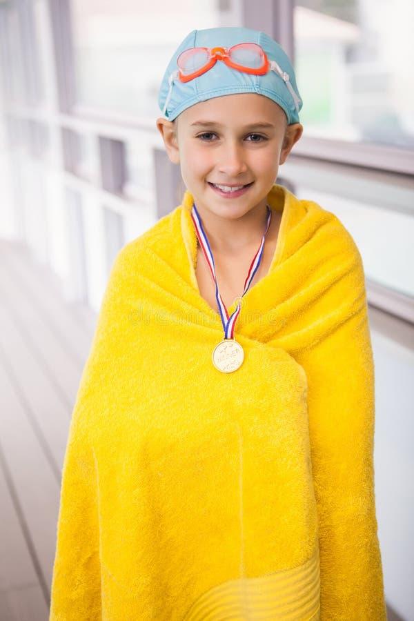 Χαριτωμένο poolside στάσης μικρών κοριτσιών που τυλίγεται στην πετσέτα στοκ φωτογραφίες