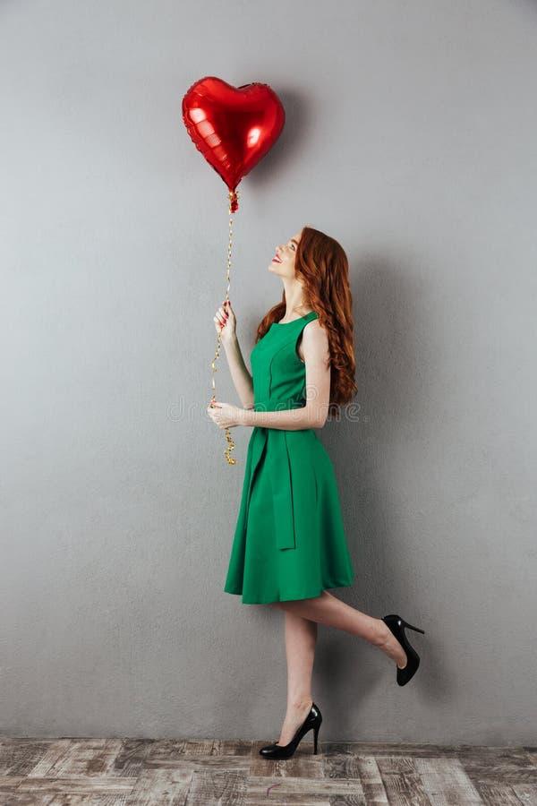 Χαριτωμένο redhead νέο μπαλόνι καρδιών εκμετάλλευσης γυναικών στοκ εικόνες