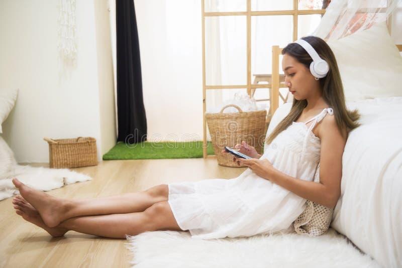 χαριτωμένο smartphone παιχνιδιού κοριτσιών στην κρεβατοκάμαρα στοκ εικόνες