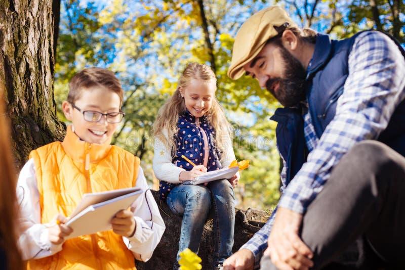 Χαρούμενα συμπαθητικά παιδιά που εξετάζουν τις σημειώσεις τους στοκ εικόνα