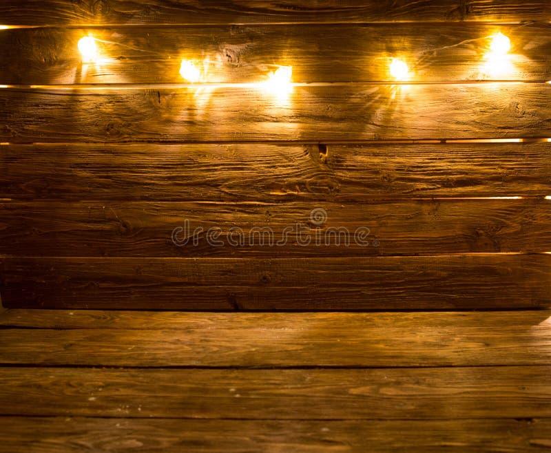 Χαρούμενα Χριστούγεννα! Ελαφρύ υπόβαθρο Χριστουγέννων στο καφετί αγροτικό ξύλινο υπόβαθρο στοκ φωτογραφία