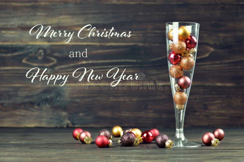 Χαρούμενα Χριστούγεννα και κάρτα καλής χρονιάς με τις σφαίρες Χριστουγέννων μέσα στοκ φωτογραφίες