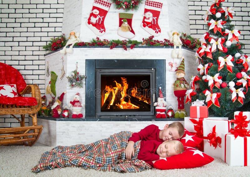 Χαρούμενα Χριστούγεννα και καλές διακοπές! Ύπνος δύο αδελφών στο καθιστικό στο πάτωμα κάτω από το δέντρο Σε αναμονή για τα δώρα α στοκ εικόνες