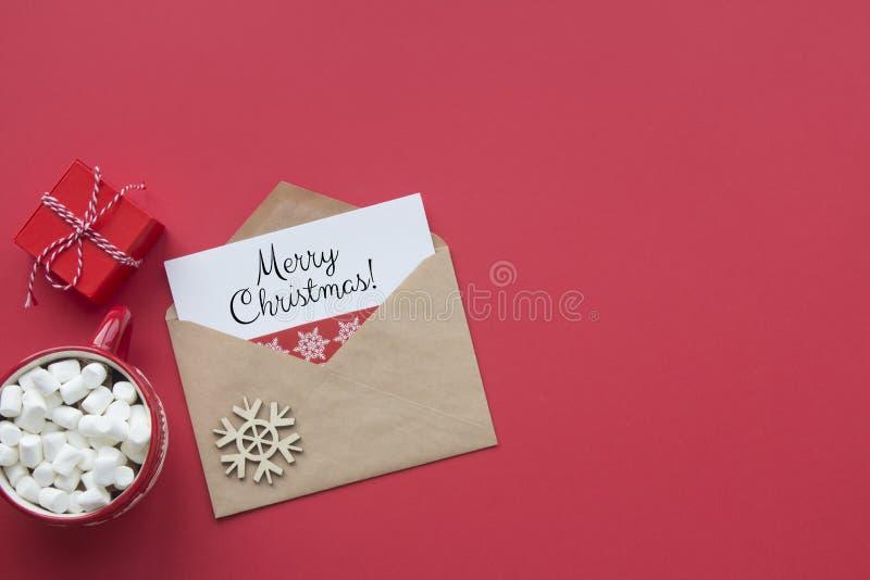 Χαρούμενα Χριστούγεννα κόκκινη κάρτα στην κορυφή Φάκελος με ευχή, δώρο και κούπα καφέ στο κόκκινο φόντο στοκ εικόνες με δικαίωμα ελεύθερης χρήσης
