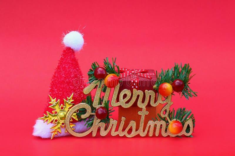 Χαρούμενα Χριστούγεννα με το καπέλο Άγιου Βασίλη και το νέο δώρο έτους με το deco στοκ εικόνες