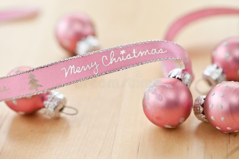 «Χαρούμενα Χριστούγεννα» που γράφεται στη ρόδινη κορδέλλα στοκ εικόνες