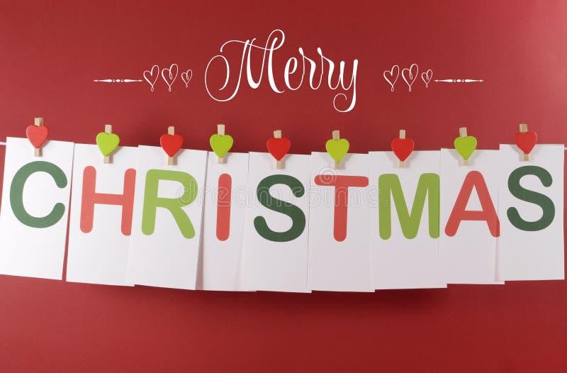 Χαρούμενα Χριστούγεννα που χαιρετά το μήνυμα στις κόκκινες και πράσινες κάρτες επιστολών που κρεμούν από τους γόμφους μορφής καρδ στοκ εικόνες με δικαίωμα ελεύθερης χρήσης