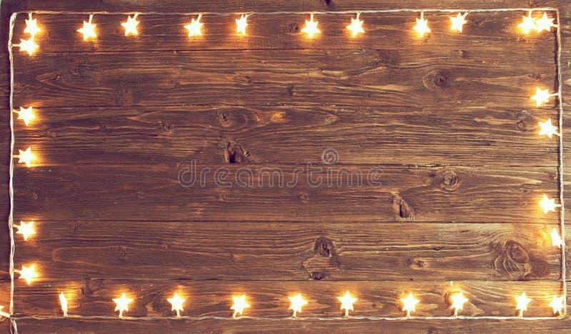 Χαρούμενα Χριστούγεννα! Τα Χριστούγεννα ανάβουν το πλαίσιο στο ξύλινο υπόβαθρο με το διάστημα αντιγράφων στοκ εικόνες
