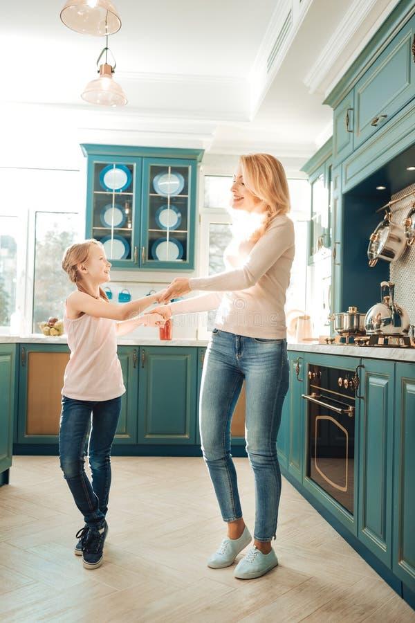 Χαρούμενα mom και κορίτσι που χορεύουν στην κουζίνα στοκ εικόνες με δικαίωμα ελεύθερης χρήσης